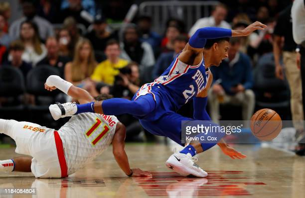 Matisse Thybulle of the Philadelphia 76ers dives for a loose ball over Trae Young of the Atlanta Hawks in the second half at State Farm Arena on...