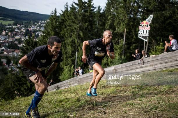 Matjaz Miklosa of Slovenia and Johan Goubau of Belgium make their way up the 400 metre skijump at Hochfirstschanze during the final of the Red Bull...