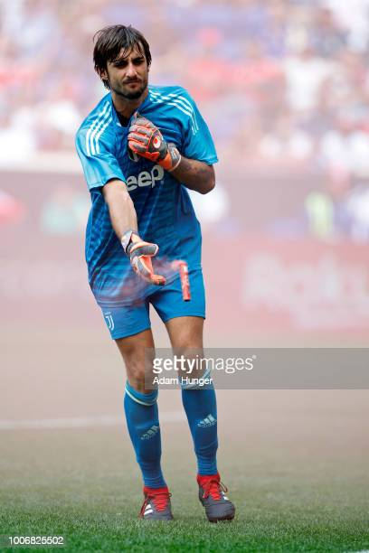 Matlia Perin of Juventus tosses a flare that was thrown onto the pitch against Benfica during the International Champions Cup 2018 match between...