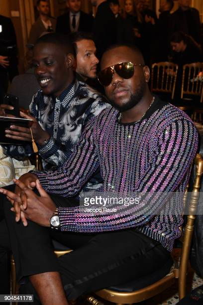 Maître Gims and a guest attend the Versace show during Milan Men's Fashion Week Fall/Winter 2018/19 on January 13 2018 in Milan Italy