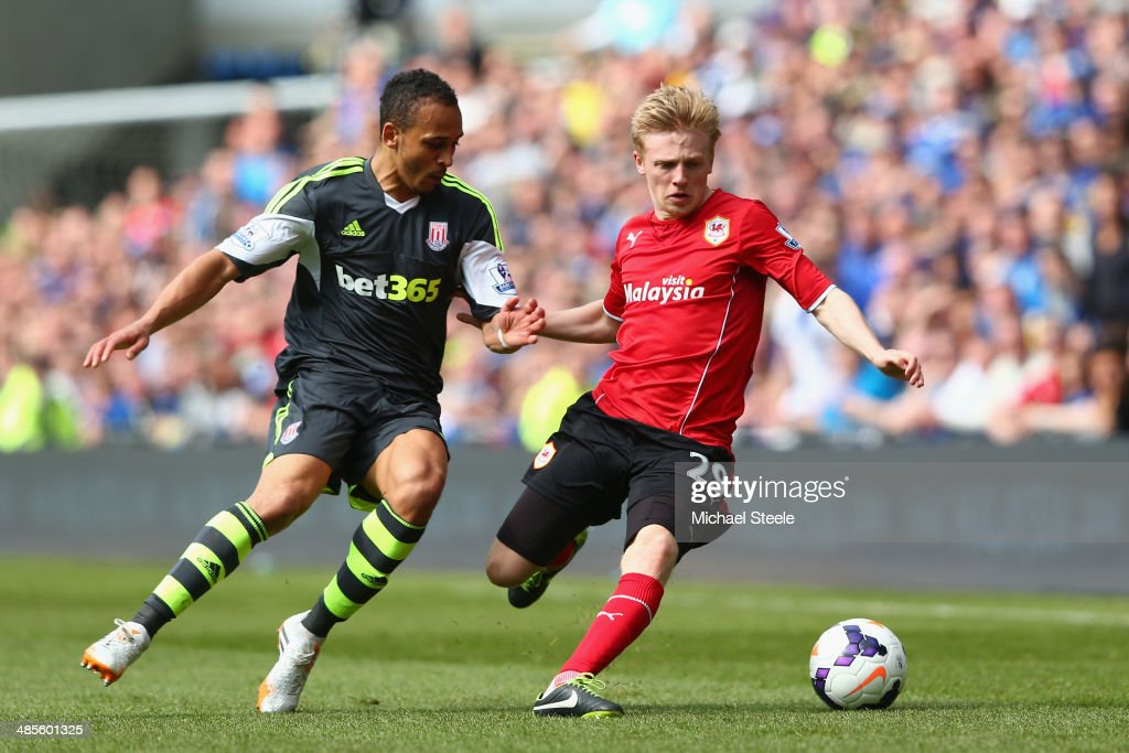 Mats Daehli (R) of Cardiff City is challenged by Peter Odemwingie (L) of Stoke City during the Barclays Premier League match between Cardiff City and Stoke City at the Cardiff City Stadium on April 19, 2014 in Cardiff, Wales.