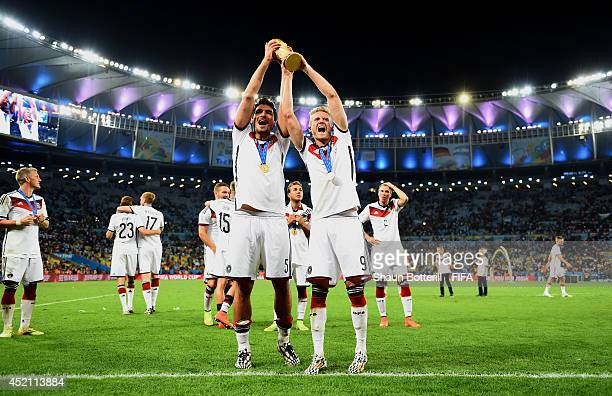 Mats Hummels and Andre Schuerrle of Germany lift the World Cup trophy to celebrate after the 2014 FIFA World Cup Brazil Final match between Germany...