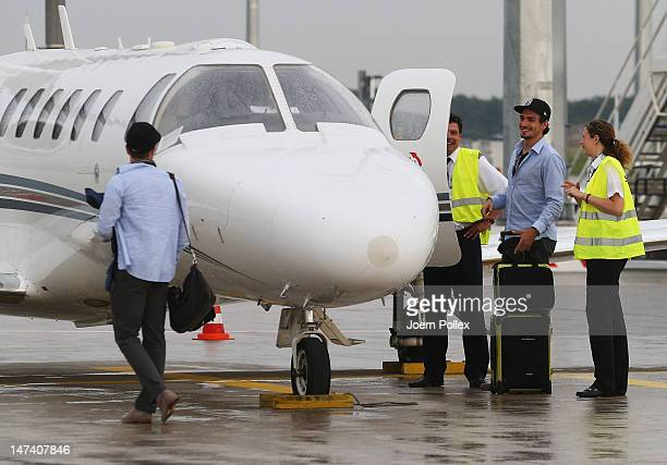 Mats Hummels and Ilkay Guendogan of Germany board a jet after they arrive at Frankfurt Airport following Germany's defeat to Italy in the semifinal...