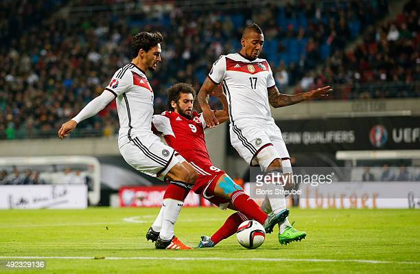 Mats Hummels and Jerome Boateng of Germany challenge Nikoloz Gelashvili of Georgia during the UEFA EURO 2016 Group D qualifying match between Germany...