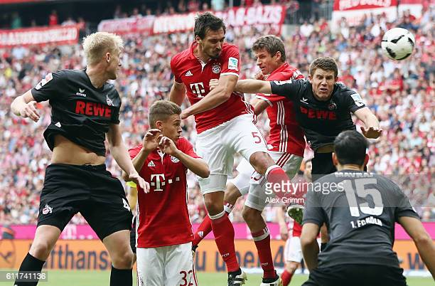 Mats Hummels and Thomas Mueller of Muenchen jump for a header with Frederik Soerensen and Dominique Heintz of Koeln during the Bundesliga match...