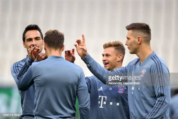 Mats Hummels Joshua Kimmich and Niklas Suele of Bayern Munich share a joke during a training session ahead of their UEFA Champions League Group E...