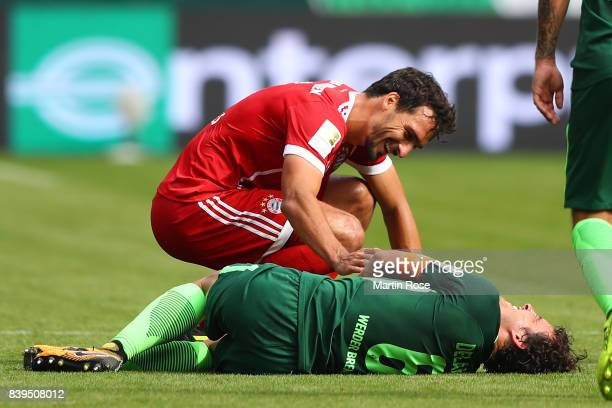 Mats Hummels of Bayern Muenchen checks on Thomas Delaney of Bremen after accidentally hitting him during the Bundesliga match between SV Werder...