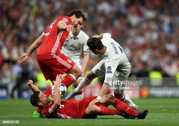 Mats Hummels of Bayern Muenchen Xabi Alonso of Bayern Muenchen and Cristiano Ronaldo of Real Madrid compete for the ball during the UEFA Champions...