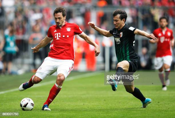 Mats Hummels of Bayern Munich is challenged by Ji DongWon of Augsburg during the Bundesliga match between Bayern Muenchen and FC Augsburg at Allianz...