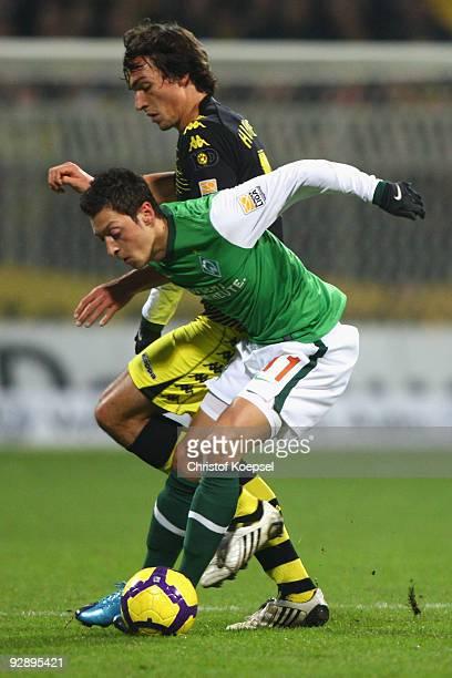 Mats Hummels of Dortmund tackles Mesut Oezil of Bremen during the Bundesliga match between SV Werder Bremen and Borussia Dortmund at the Weser...