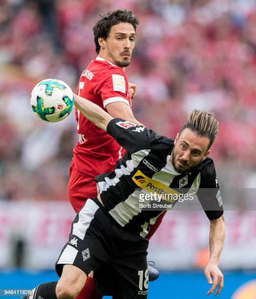 Mats Hummels of FC Bayern Muenchen jumps for a header with Josip Drmic of Borussia Moenchengladbach during the Bundesliga match between FC Bayern...