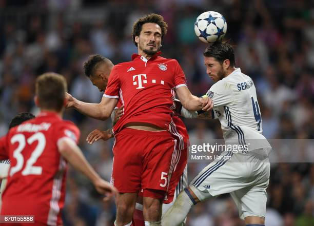 Mats Hummels of FC Bayern Muenchen jumps for a header with Sergio Ramos of Real Madrid during the UEFA Champions League Quarter Final second leg...