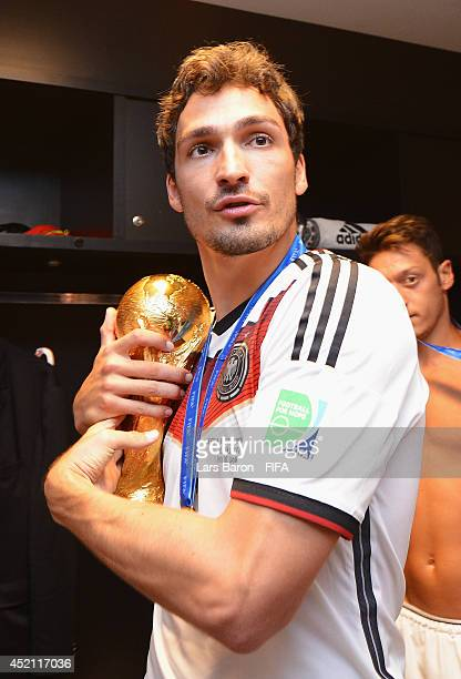 Mats Hummels of Germany holds up the World Cup trophy in the Germany dressing room after the 2014 FIFA World Cup Brazil Final match between Germany...