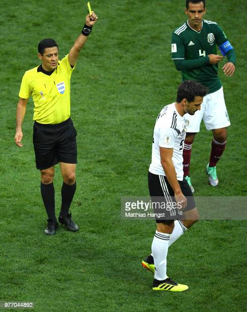 Mats Hummels of Germany is shown a yellow card by Referee Alireza Faghani during the 2018 FIFA World Cup Russia group F match between Germany and...