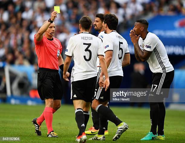Mats Hummels of Germany is shown a yellow card by referee Szymon Marciniak during the UEFA EURO 2016 round of 16 match between Germany and Slovakia...
