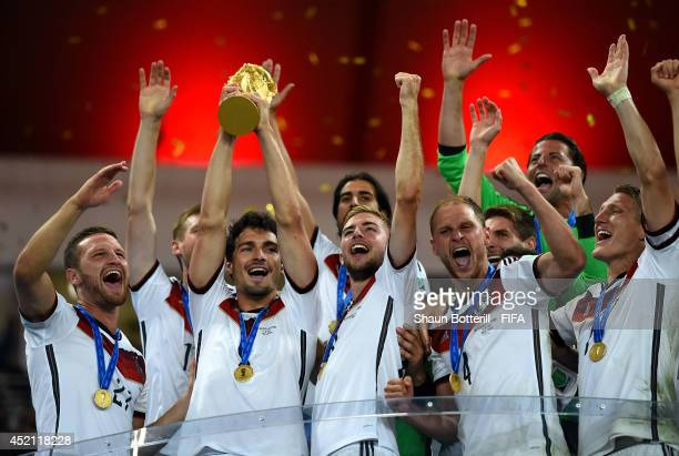 Mats Hummels of Germany lifts the World Cup trophy to celebrate with his teammates during the award ceremony after the 2014 FIFA World Cup Brazil...