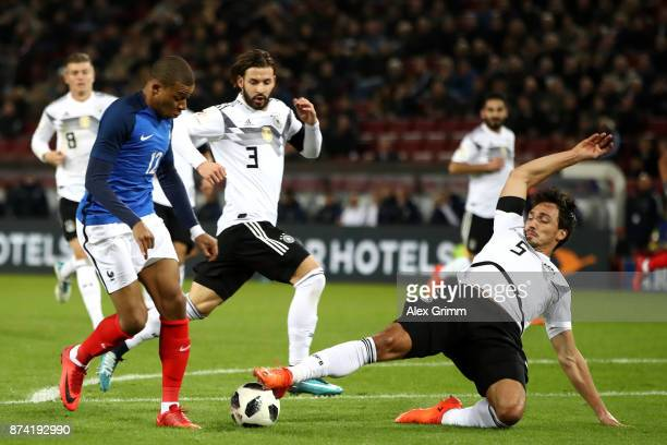 Mats Hummels of Germany tackles Kylian Mbappe of France during the international friendly match between Germany and France at RheinEnergieStadion on...