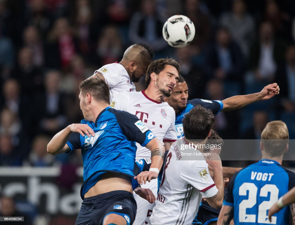 Mats Hummels of Muenchen (C) and Arturo Vidal (L) jump for a header with Jeremy Toljan of Hoffenheim during the Bundesliga match between TSG 1899 Hoffenheim and Bayern Muenchen at Wirsol Rhein-Neckar-Arena on April 4, 2017 in Sinsheim, Germany.