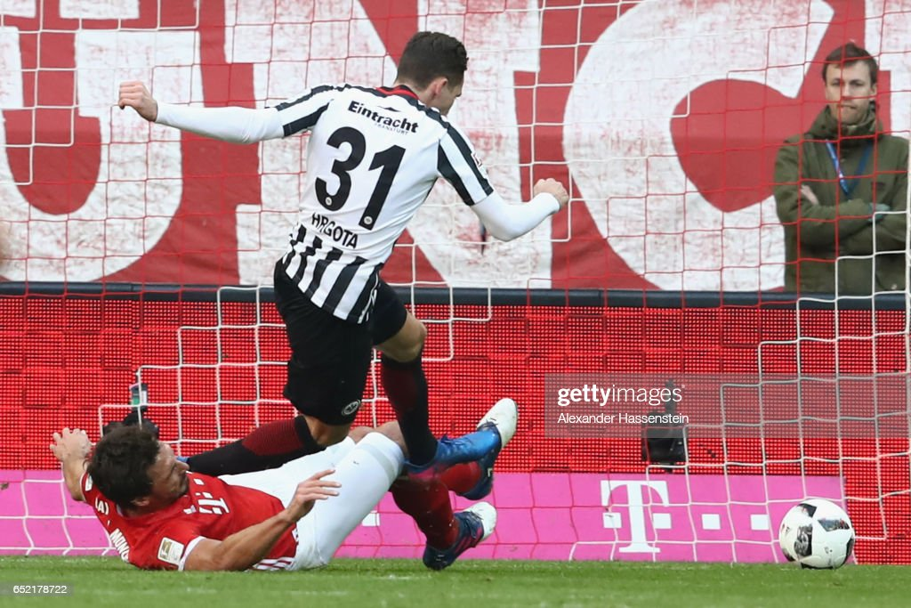 Mats Hummels (L) of Muenchen battles for the ball with Branimir Hrgota of Frankfurt during the Bundesliga match between Bayern Muenchen and Eintracht Frankfurt at Allianz Arena on March 11, 2017 in Munich, Germany.