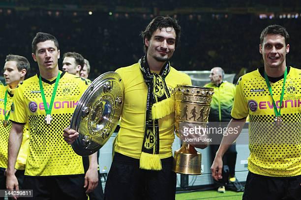 Mats Hummels Sebastian Kehl and Robert Lewandowski of Dortmund celebrate with the cup after winning the DFB Cup final match between Borussia Dortmund...