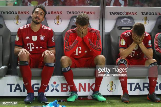 Mats Hummels Thomas Mueller and Joshua Kimmich of Bayern Muenchen are dejected after losing the DFB Cup final against Eintracht Frankfurt at...