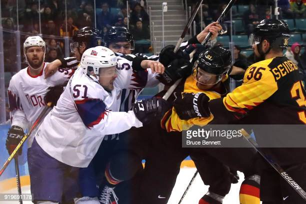 Mats Rosseli Olsen of Norway and Moritz Muller of Germany collide in the first period during the Men's Ice Hockey Preliminary Round Group B game on...