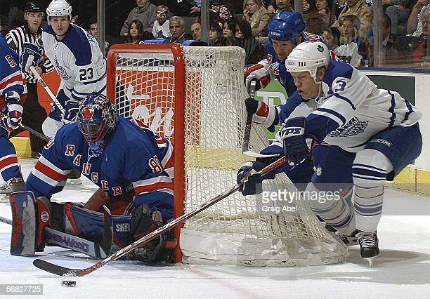 Mats Sundin of the Toronto Maple Leafs attempts a wrap-around shot against goalie Kevin Weekes and Michael Nylander of the New York Rangers during...