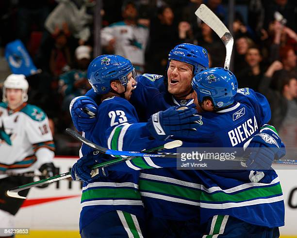 Mats Sundin of the Vancouver Canucks celebrates his first goal as a member of the Canucks with teammates Alex Edler and Kevin Bieksa during their...