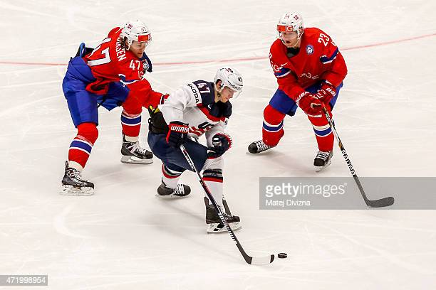 Mats Trygg and Alexander Bonsaksen of Norway and Torey Krug of USA battle for the puck during the IIHF World Championship group B match between...