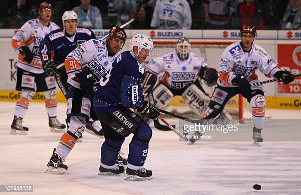 Mats Trygg of Hamburg vies for the puck with Robert Hock of Iserlohn during the DEL match between Hamburg Freezers and Iserlohn Roosters at the O2...