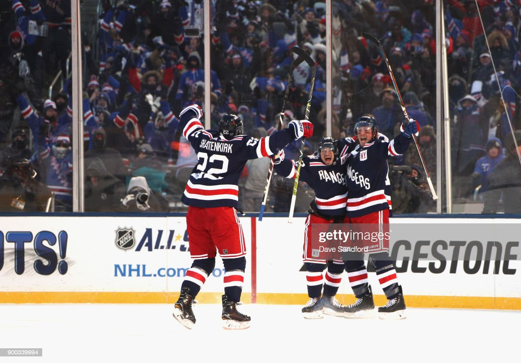 Mats Zuccarello #36, J.T. Miller #10 and Kevin Shattenkirk #22 of the New York Rangers celebrate after Miller scored the game-winning goal in overtime against the Buffalo Sabres during the second period of the 2018 Bridgestone NHL Winter Classic between the New York Rangers and the Buffalo Sabres at Citi Field on January 1, 2018 in the Flushing neighborhood of the Queens borough of New York City.