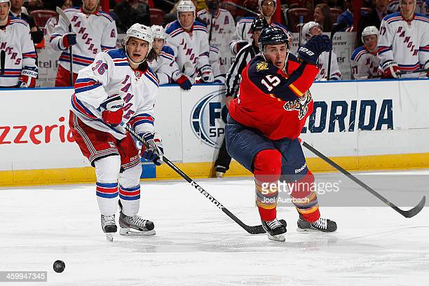 Mats Zuccarello of the New York Rangers and Drew Shore of the Florida Panthers chase a loose puck at the BBT Center on December 31 2013 in Sunrise...