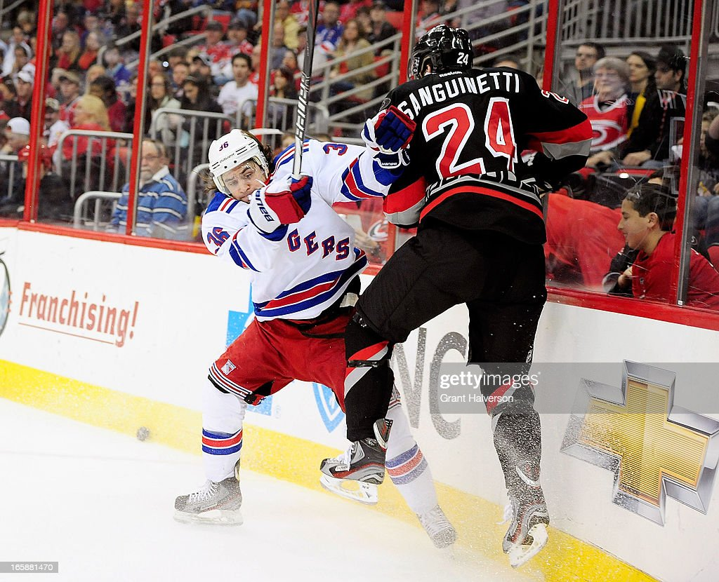 Mats Zuccarello #36 of the New York Rangers knocks Bobby Sanguinetti #24 of the Carolina Hurricanes off of the puck during play at PNC Arena on April 6, 2013 in Raleigh, North Carolina.