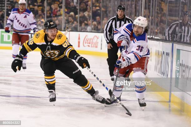 Mats Zuccarello of the New York Rangers passes the puck against David Pastrnak of the Boston Bruins at the TD Garden on December 16 2017 in Boston...