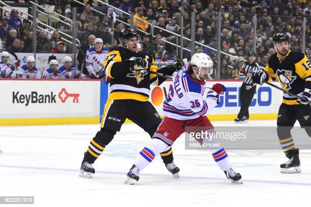Mats Zuccarello of the New York Rangers pushes Sidney Crosby of the Pittsburgh Penguins at PPG PAINTS Arena on January 14 2018 in Pittsburgh...