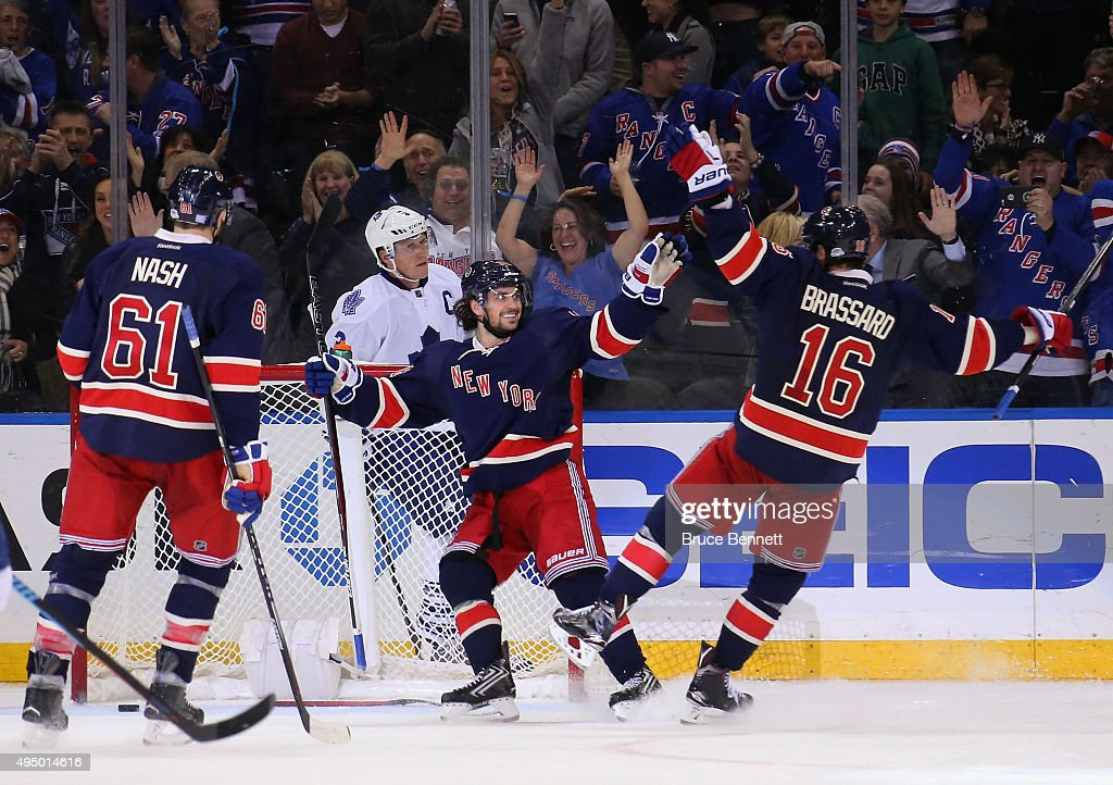 Mats Zuccarello #36 of the New York Rangers (c) scores his third goal of the game at 19:11 of the third period against the Toronto Maple Leafs and is joined by Rick Nash #61 (l) and Derick Brassard #16 (r) at Madison Square Garden on October 30, 2015 in New York City. The Rangers defeated the Maple Leafs 3-1.