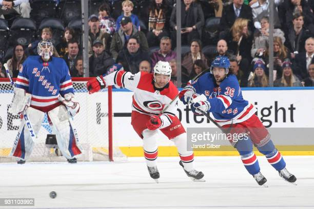 Mats Zuccarello of the New York Rangers skates with the puck against Justin Williams of the Carolina Hurricanes at Madison Square Garden on March 12...