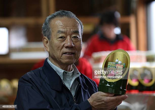 Matsui Kouji master and owner of doll shop shows Kaguyabina a pair of paper dolls placed inside a bamboo container for Hinamatsuri at Matsui Kogeisha...