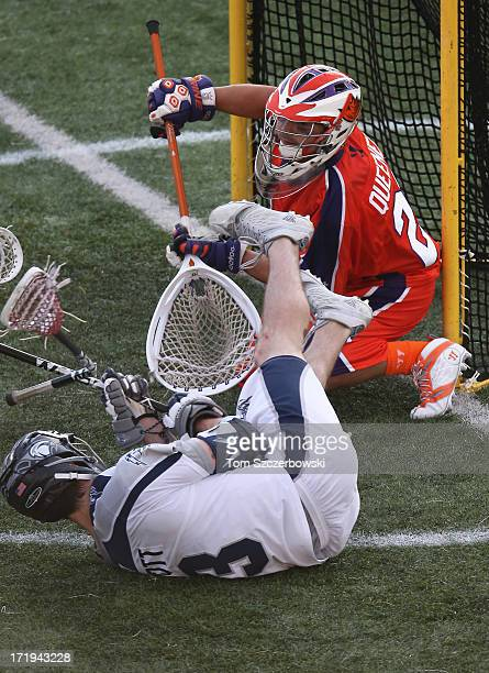 Matt Abbott of the Chesapeake Bayhawks falls in front of the net during Major League Lacrosse game action as Brett Queener of the Hamilton Nationals...