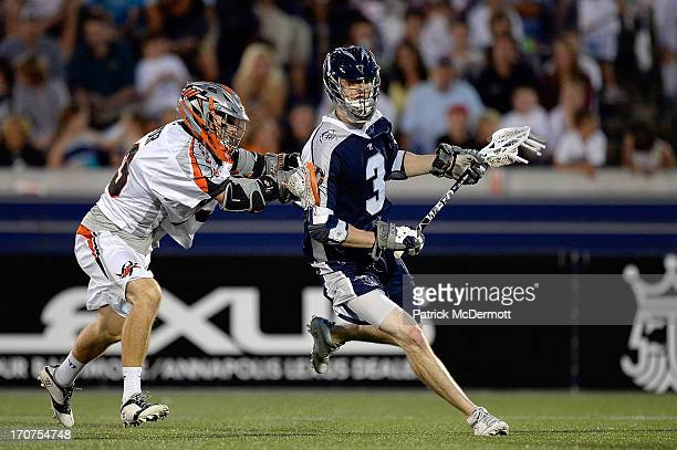 Matt Abbott of the Chesapeake Bayhawks runs past Drew Snider of the Denver Outlaws during a game at NavyMarine Corps Memorial Stadium on June 15 2013...