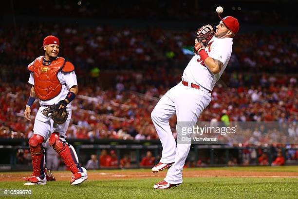 Matt Adams of the St Louis Cardinals catches a bunt attempt against the Cincinnati Reds in the second inning as Yadier Molina of the St Louis...