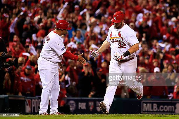 Matt Adams of the St. Louis Cardinals celebrates with third base coach Jose Oquendo after hitting a solo home run in the eighth inning against the...