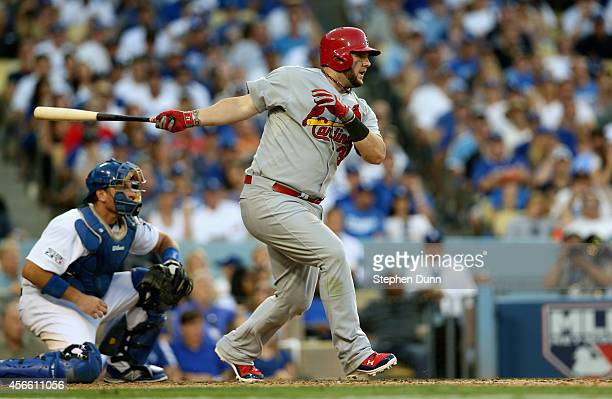 Matt Adams of the St Louis Cardinals hits a RBI single in the seventh inning against the Los Angeles Dodgers during Game One of the National League...
