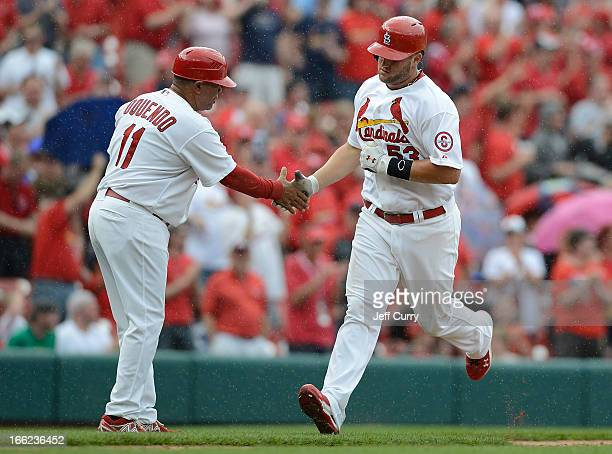 Matt Adams of the St Louis Cardinals is congratulated by third base coach Jose Oquendo after hitting a two run home run off of Homer Bailey of the...