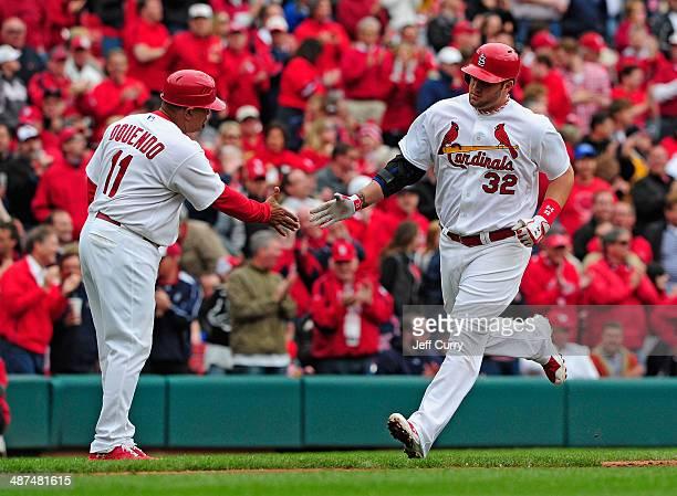 Matt Adams of the St Louis Cardinals is congratulated by third base coach Jose Oquendo after hitting a three run home run off of Matt Garza of the...