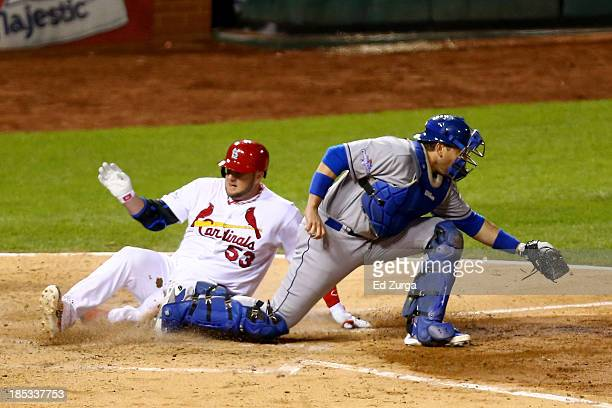 Matt Adams of the St. Louis Cardinals slides home safely before catcher A.J. Ellis of the Los Angeles Dodgers gets the ball in the fifth inning in...