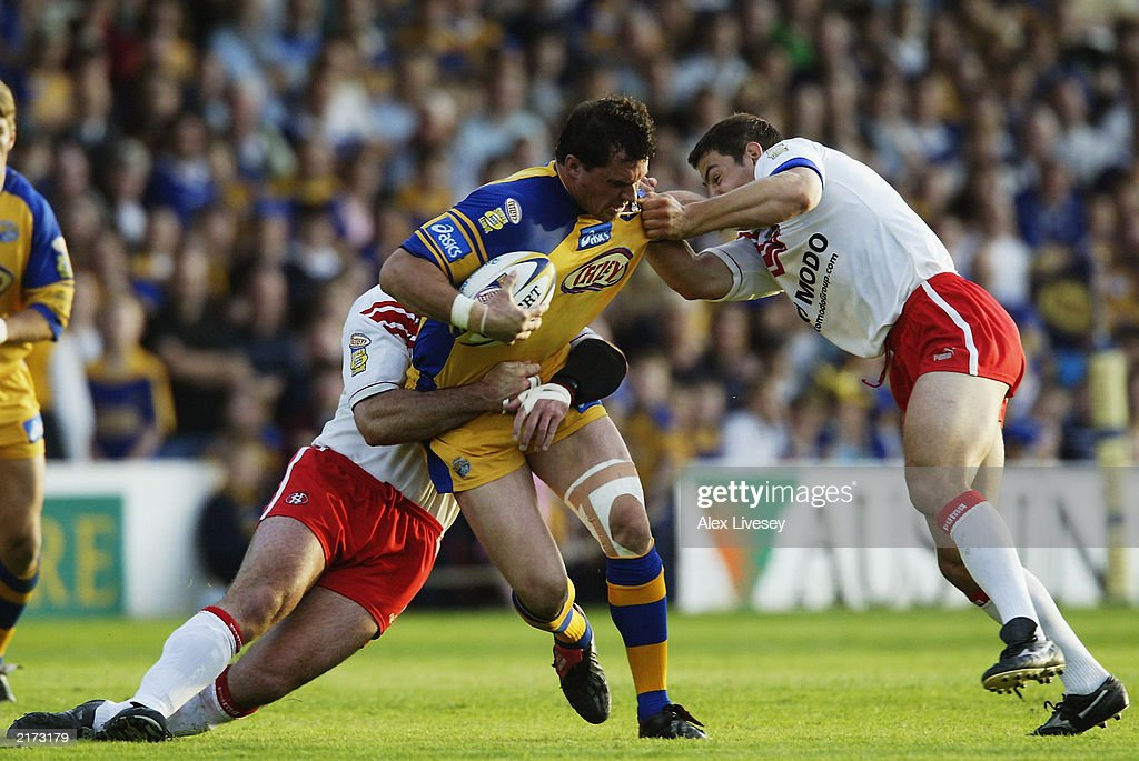 Matt Adamson of Leeds Rhinos is wrapped up by Chris Joynt and Mike Bennett of St Helens during the Tetley's Super League match between Leeds Rhinos and St Helens held on June 13, 2003 at the Headingley Stadium in Leeds, England. Leeds Rhinos won the match 20-14.