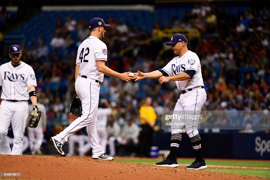 Matt Andriese #35 passes off the ball to pitching coach Kyle Snyder #23 of the Tampa Bay Rays during the eighth inning against the Philadelphia Phillies on April 15, 2018 at Tropicana Field in St Petersburg, Florida. All players are wearing #42 in honor of Jackie Robinson Day.