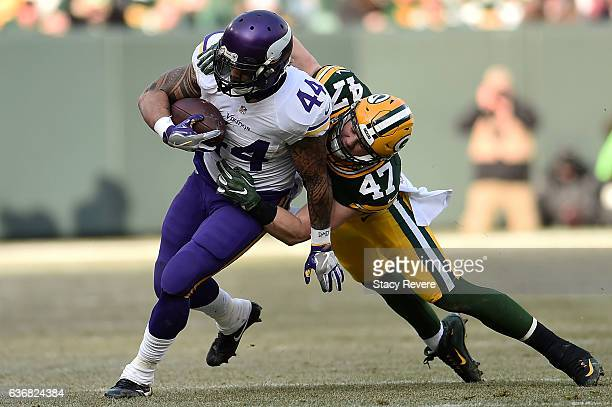 Matt Asiata of the Minnesota Vikings is pursued by Jake Ryan of the Green Bay Packers during a game at Lambeau Field on December 24 2016 in Green Bay...