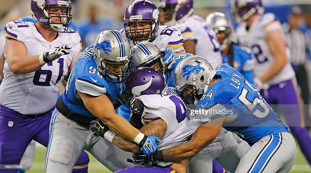 Matt Asiata #44 of the Minnesota Vikings is stopped by Ndamukong Suh #90 and DeAndre Levy #54 of the Detroit Lions during the third quarter of the game at Ford Field on December 14, 2014 in Detroit, Michigan. The Lions defeated the Vikings 16-14.